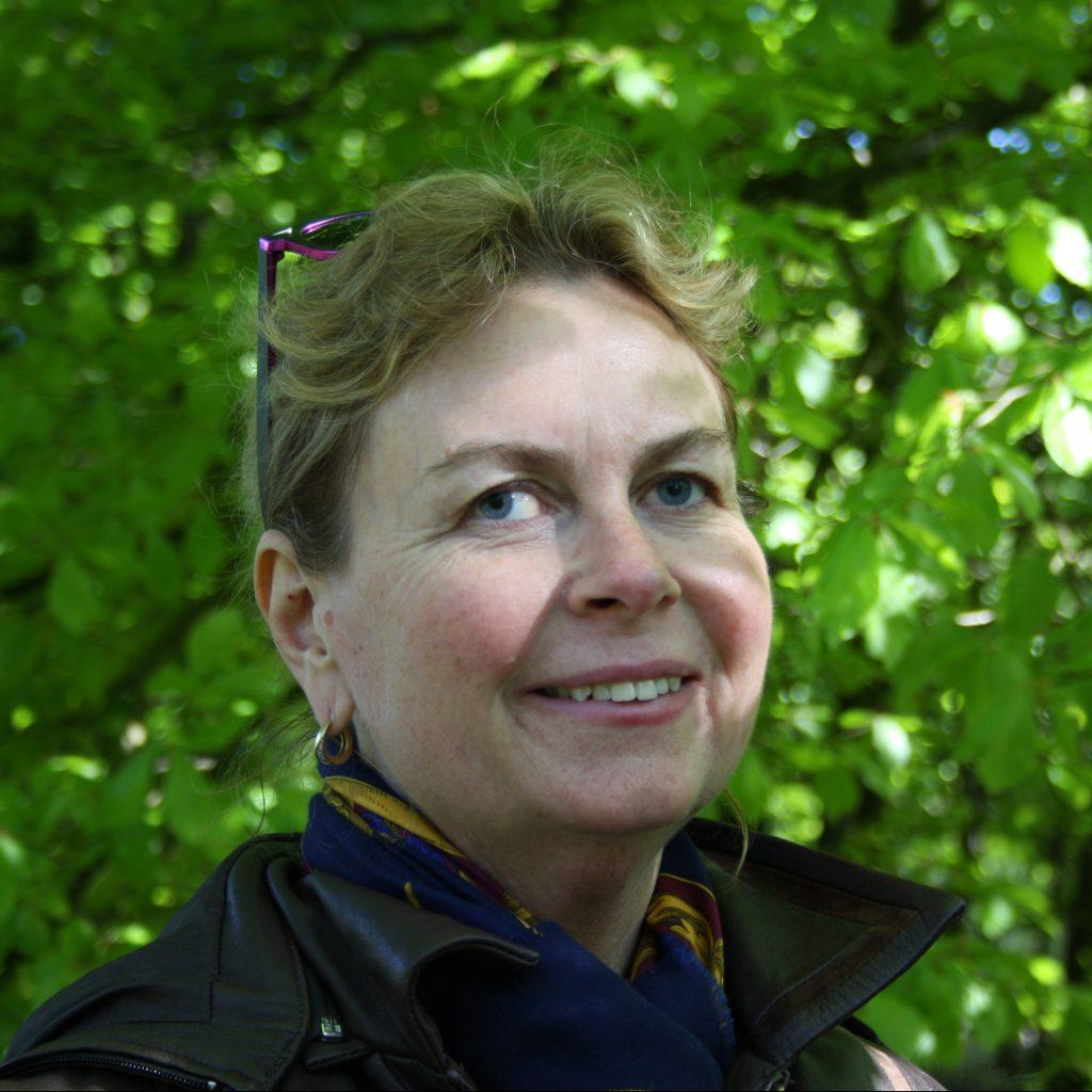Bild på Monica med grönska i bakgrunden